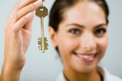 Key to the future. Smiling business woman is holding the key Royalty Free Stock Image