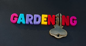 Key to gardening. Text ' gardening' in colorful uppercase letters with a gold key replacing the letter 'i', dark background Stock Images