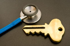 Key to good health. A macro image of a gold key and stethoscope on a dark background. A concept image of the key to good health and possible logo Royalty Free Stock Photos