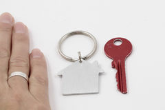 The key to a good marriage. Key and hand with wedding ring close up as symbol of key to a good marriage Royalty Free Stock Image