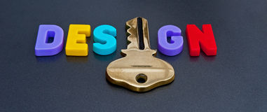 Key to great design. Shown as colorful upper case letters with the 'i' replaced by a golden key on a plain dark background Stock Photo