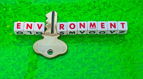 Key to a green environment. Text 'environment' in uppercase red letters inscribed on small white cubes with letter'i' replaced with a gold key, green background Royalty Free Stock Photography