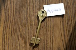 The key to happiness of bronze color. On a wooden background Royalty Free Stock Photography
