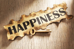 Key to happiness concept. Using burnt paper with word happiness printed on it and golden key placed on its side Stock Images