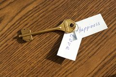 The key to happiness and love of bronze color. On a wooden background Stock Photos