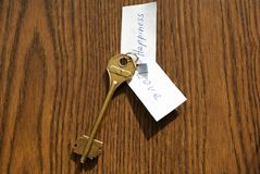The key to happiness and love of bronze color. On a wooden background Royalty Free Stock Photography