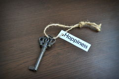 The key to happiness. Key on the table with a note written on it key to happiness; key to happiness Royalty Free Stock Photo