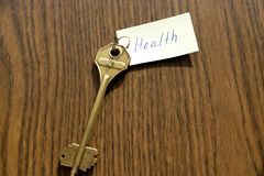 The key to health of bronze color. On a wooden background Royalty Free Stock Photography