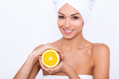 The key to a healthy smile!. A young woman wrapped in white towel holding an orange and smiling at the camera Stock Image