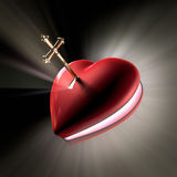 Key to the heart. A cross shaped key unlocking a heart shaped box opening witth volume light shooting out Stock Images