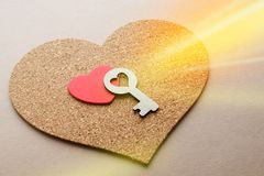 Key to the heart as a symbol of love. Two red hearts from different materials one inside another with key, symble of love, patch of day light Royalty Free Stock Photo