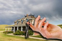Key To The House. A hand holding a skeleton key in front of an old masion Royalty Free Stock Images
