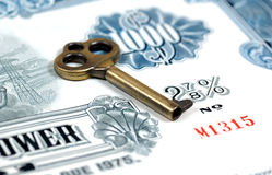 Key To Investing. Key and a Stock Certificate.  Key To Investing Concept Royalty Free Stock Photo