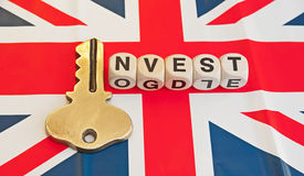Key to investing in Britain. Union Jack flag with text ' invest ' in black uppercase letters on small white cubes with letter ' i ' replaced by a gold key Royalty Free Stock Photos