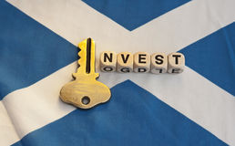 Key to investing in Scotland. Scottish flag, the saltire,  with text ' invest ' in black uppercase letters on small white cubes with letter ' i ' replaced by a Stock Image