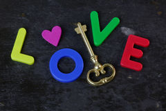 Key to Love. Antique key on a slate background with the word love in letters Royalty Free Stock Image
