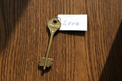 The key to love of bronze color. On a wooden background Royalty Free Stock Image
