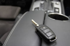 Key to a luxury car. Car key to a German luxury car, the key is lying on dark leather Royalty Free Stock Image