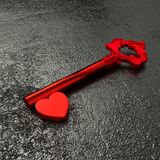 The key to my heart concept illustration. Red vintage key with a shiny heart on a rough black stone table 3D illustration Stock Photo