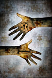 Key To The Mystery. Hand holding a key alongside second hand holding a jigsaw piece with keyhole in centre against a grunge background of layered jigsaw pieces Stock Photos