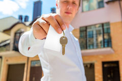 Key to a new apartment in the hands of sales agent. The key to a new apartment in the hands of sales agent Royalty Free Stock Image