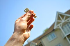Key to new home. Male hand holding a key to a house Royalty Free Stock Photos