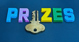 Key to prizes. Text ' prizes ' in colorful upper case letters with a gold key replacing the letter 'i' isolated on a dark background Stock Images