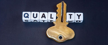 """Key to quality. Text """"quality"""" in black upper case letters on small white cubes but with letter 'i' replaced by gold key, dark background Royalty Free Stock Photography"""