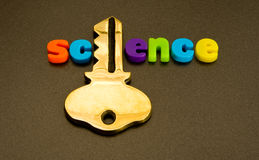 Key to science. A macro image of the word science in colorful lower case letters but where the 'i' has been replaced by a large gold key