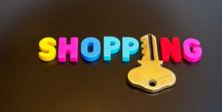 Key to shopping. Text ' shopping ' in colorful uppercase text  with letter ' i ' replaced by a golden key on a dark background Royalty Free Stock Photography
