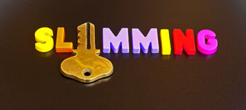 Key to slimming. Text ' slimming ' in colorful uppercase letters with the ' i ' replaced by a gold key isolated on a dark background Royalty Free Stock Photos