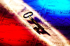 Key To Success. Photo of a Key and Stock Charts With Colored Gel Lighting Royalty Free Stock Photos