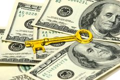 Key to Success. Golden key on top of US dollar bills Stock Photography