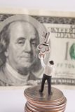 Key To Success. Miniature man holding antique key. Hundred dollar bill in background Royalty Free Stock Images