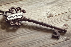 Key to success. Antique key with word success written on paper resting on wooden surface concept for aspirations and success Stock Photo