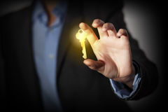 Key to success. Close up of human hand catching golden key Royalty Free Stock Images