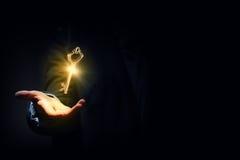 Key to success. Close up of human hand holding golden key Stock Photos