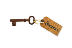 Key to success. Close up of an old key with a success tag, business concept on a white background royalty free stock photos