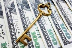 Key to success. Closeup of gold key on hundred dollar bills Stock Image