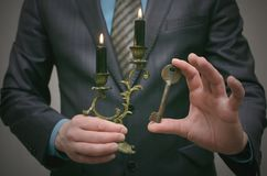 Key to success concept. Businessman holding in hands an old rusty key and a burning candle in candlestick. Explanation of information decryption key. Access to Stock Photography