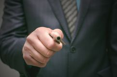 Key to success concept. Businessman holding in hands an old rusty key and opens the door, front view. stock photography