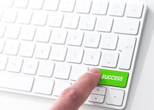 Key to success. Finger pressing a green key labeled SUCCESS on a computer keyboard, key to success Royalty Free Stock Images