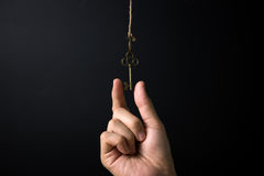 Key to success or key opportunity concept. Hand reaching out for key over black background Stock Photos