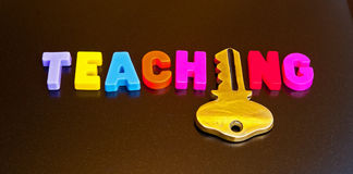 Key to teaching. Text ' teaching ' in colorful  uppercase letters with the letter 'i' replaced by a gold key isolated on a dark background Stock Photography