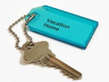 Key to Vacation Home. Door key to vacation home attached to a tag with a metal ball chain Royalty Free Stock Photography