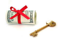 Key to wealth. Roll of hundred dollar bills tied with ribbon next to a golden key Stock Photography