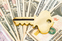Key to wealth creation ?. A gold key placed on top of a pile of mainly ten Dollar bills. A concept image of successful wealth creation Royalty Free Stock Images