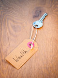 Key to wealth. Old key on a string with retro brown paper label reading wealth on an aged woodgrain background. Secret to successful life  concept Royalty Free Stock Photos