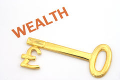 Key to wealth - pounds. A gold key with a pound symbol on it. Something to unlock your wealth with Royalty Free Stock Images