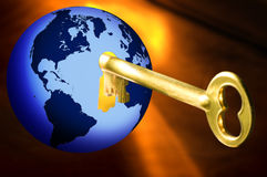 Key to the world. Golden key opening a blue globe with world map on warm yellow background Stock Photos